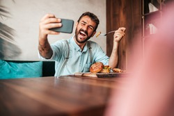 Handsome middle age man sitting in restaurant and enjoying in delicious burger. He is happy, smiled and using his smart phone for food photography shots.