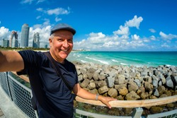 Handsome middle age man taking a selfie while enjoying Miami Beach.
