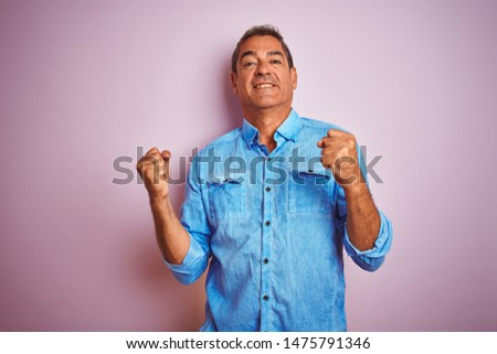 Handsome middle age man wearing blue denim shirt standing over isolated pink background very happy and excited doing winner gesture with arms raised, smiling and screaming for success.