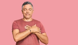 Handsome middle age man wearing casual clothes smiling with hands on chest with closed eyes and grateful gesture on face. health concept.