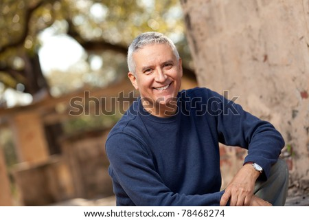 Handsome middle age man with gray hair in an outdoor setting.