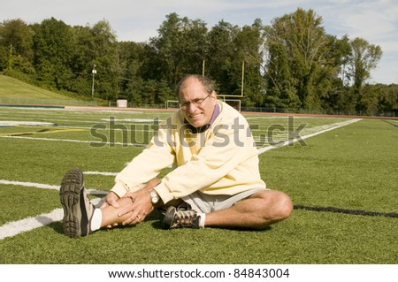 handsome middle age senior man stretching exercising on sports field