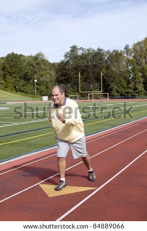 handsome middle age senior man stretching exercising running jogging on sports football field and running track