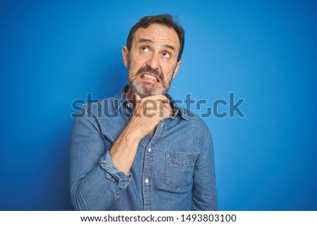 Handsome middle age senior man with grey hair over isolated blue background Thinking worried about a question, concerned and nervous with hand on chin