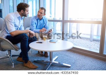 Handsome middle-aged business executive sitting with a younger coworker in a bright modern office, explaining some information to him on a digital tablet