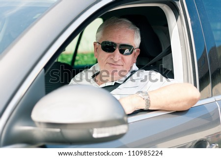 Handsome middle-aged man driving a modern car