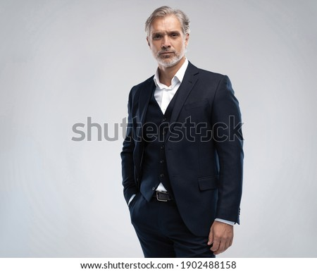 Handsome middle-aged man in suit posing against grey background