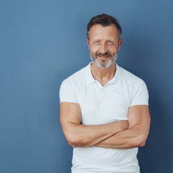 Handsome middle-aged man in white polo shirt, standing with his arms folded, looking at camera and smiling. Half-length front portrait against blue background with copy space