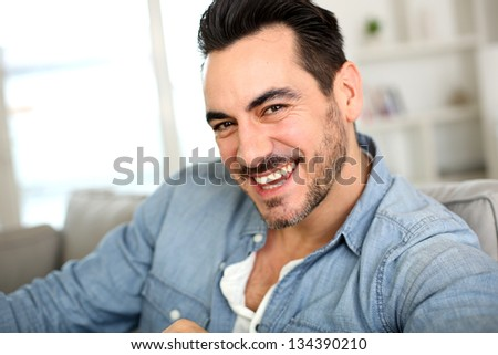Handsome middle-aged man relaxing in sofa