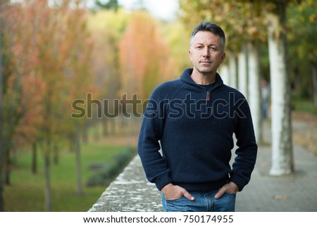 Handsome middle-aged man walking autumn park. Urban male portrait, image toned and noise added.