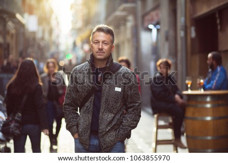 Handsome middle-aged man walking autumn street. Urban male portrait. #1063855970