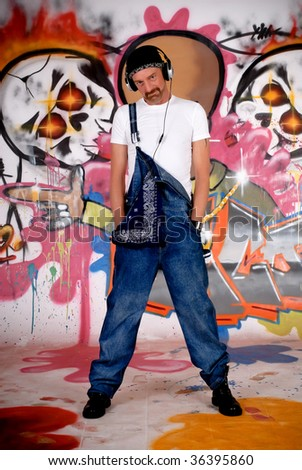 Handsome middle aged man with headset in front of graffiti wall, urban setting.  Studio shoot.