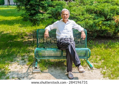 Handsome middle-aged man with salt pepper hair dressed with white shirt, blue slacks and beige moccasins is resting on a bench in city park keeping his arms opened: he shows a reassuring look #284196731