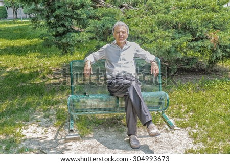 Handsome middle-aged man with salt pepper hair dressed with white shirt, blue slacks and beige moccasins is resting on a bench in city park keeping his arms opened: he smiles showing a reassuring look #304993673