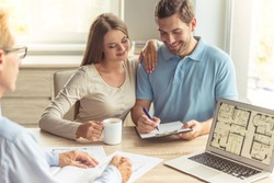 Handsome middle aged realtor in classic shirt and eyeglasses and happy young couple are discussing new house. Couple is drinking coffee, making notes and smiling while sitting in office