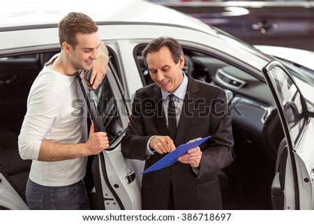 Handsome middle aged salesman is presenting a car to handsome young customer in a motor show #386718697