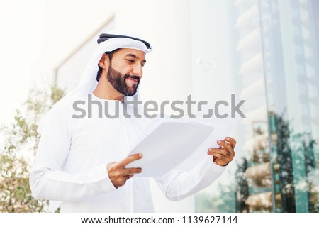 Handsome middle eastern arab businessman holding documents