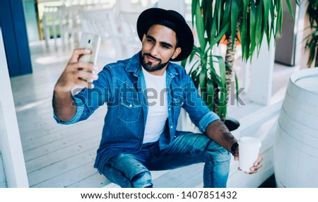 Handsome millennial guy holding takeaway cup with caffeine beverage and clicking selfie pictures, Turkish male blogger photographing himself for creating content publication on fashion web page #1407851432