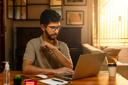 Handsome model with beard at his workplace. Home office concept.