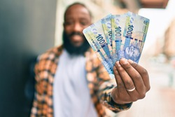 Handsome modern african american man with beard smiling positive standing at the street showing 100 south african rands banknotes
