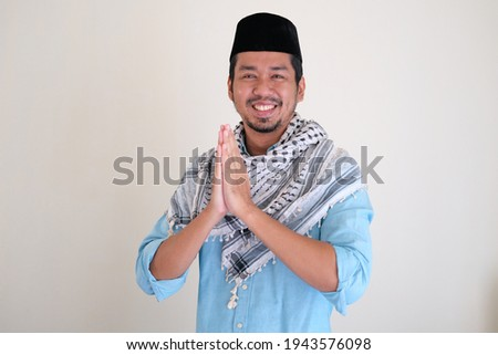 Handsome Moslem Asian man smiling while doing hand praying gesture