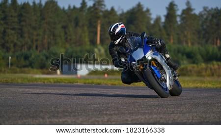 Handsome motorcyclist in black riding his super sport motorcycle. european road racing championship. Unknown pilot. Racing MotoGP Team. Sport Biker Racing on Road Stock foto ©