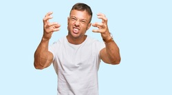 Handsome muscle man wearing casual white tshirt shouting frustrated with rage, hands trying to strangle, yelling mad