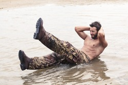 Handsome Muscled Soldier with no Shirt Doing Curl Ups Exercise at the Sea Water