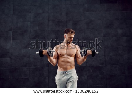 Handsome muscular caucasian blond shirtless man lifting dumbbells while standing in front of dark background.
