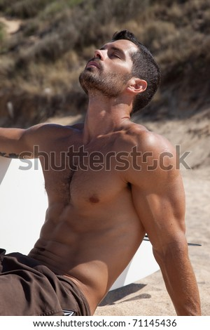 Handsome muscular dark haired surfer sitting on the sand next to his board, wearing a brown bathing suit.