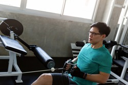 Handsome Muscular Fitness asian man in the gym, training hard and pulling weights in seated cable row machine, Athlete makes exercise, Bodybuilder, Sport fitness and muscles concept