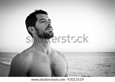 Handsome muscular man deep breathing on the beach. Black and white portrait.