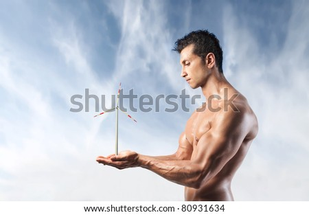 Handsome muscular man holding a windmill in his hands