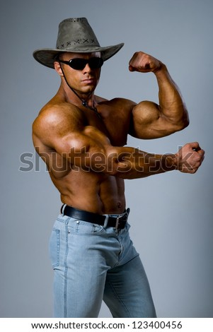 Handsome muscular man in a hat showing his muscles on a gray background