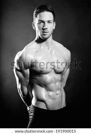 handsome muscular man in black and white on black background