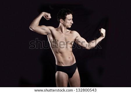 Handsome muscular man on black background
