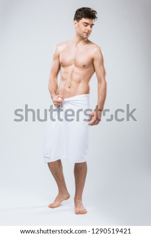 handsome muscular man posing in towel isolated on grey