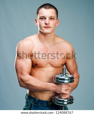 Handsome muscular man use his dumbbell to exercise