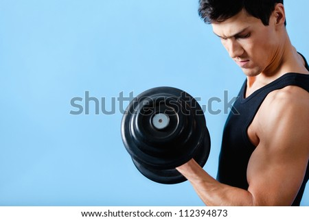 Handsome muscular man uses his dumbbell to exercise flexing bicep muscle
