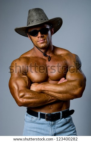 Handsome muscular man with a hat on a gray background