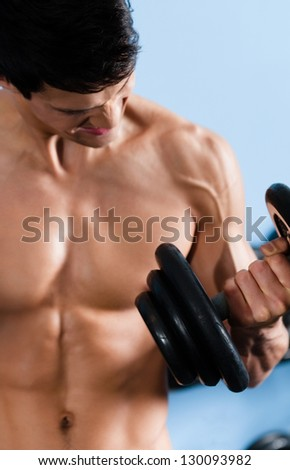 Handsome muscular man with naked body uses his dumbbell to exercise flexing bicep muscle