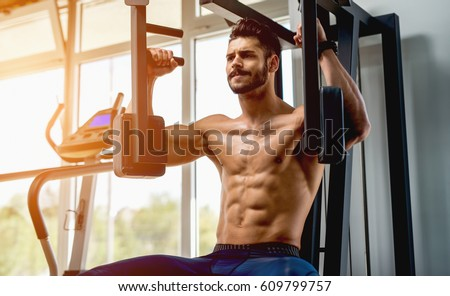 Handsome muscular man working out hard at gym. Training without shirt. Chest exercises. Chest workouts. Stock photo ©