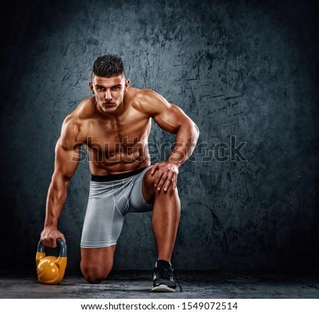Handsome Muscular Men Exercise With Kettlebell. Cross training athlete