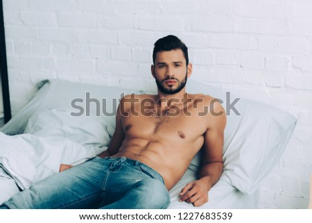 handsome muscular shirtless man in jeans posing on bed at home
