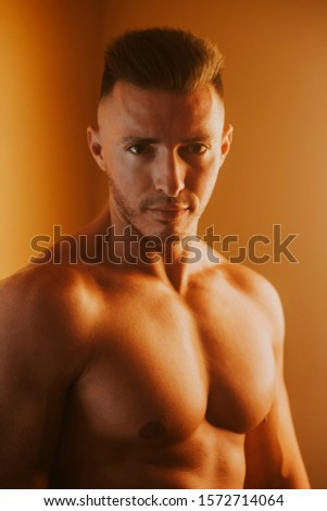 Handsome muscular shirtless young man looking at camera, orange light, vertical format