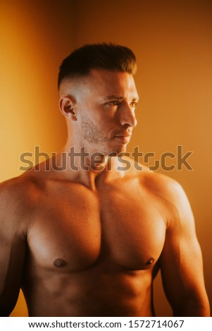 Handsome muscular shirtless young man looking to the right, orange light, vertical format