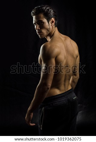 Handsome muscular shirtless young man standing confident, profile view, looking at camera
