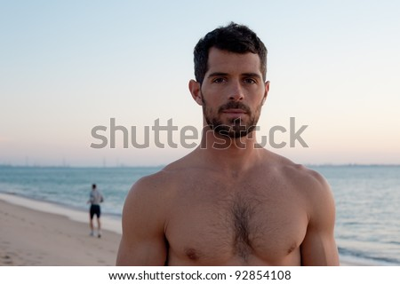 Handsome muscular sport man on the beach, with man running in the ...