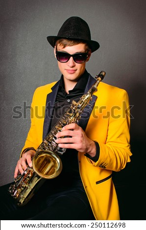Handsome musician saxophonist with saxophone. Young saxophone player in studio. Jazz-band