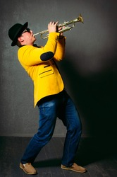 Handsome musician trumpet player playing trumpet at studio. Jazz-band